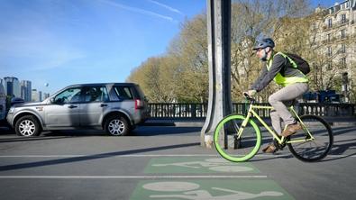 Un homme à vélo en ville, sur la portion de route qui lui est réservée