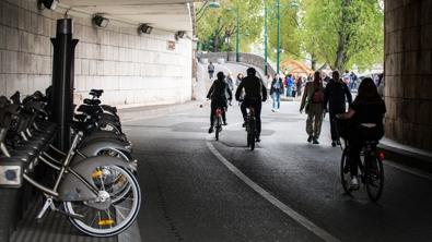 Borne de vélib sur les quais, plusieurs personnes en vélib et des promeneurs